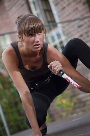 young female killer with bloody knife outdoor photo