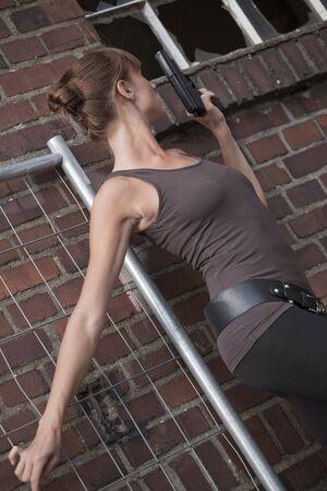 ventana rota: mujer joven con pistola mirando en la ventana rota