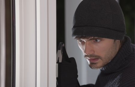 thief with crowbar breaking into a house by night Stock Photo
