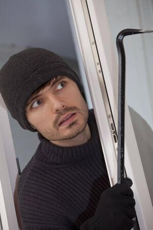 perpetrator: robber with crowbar breaking into a house Stock Photo