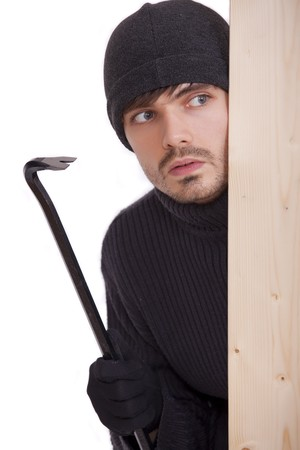 perpetrator: criminal guy with crowbar hiding behind wooden bar Stock Photo