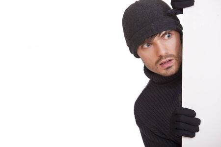 perpetrator: burglar in black hat hiding under white board - isolated Stock Photo