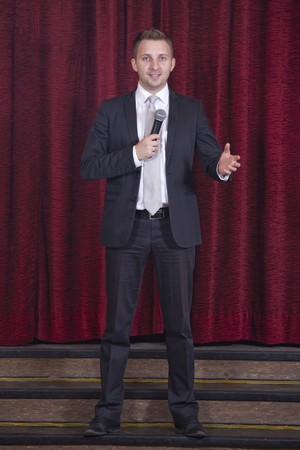 showman: locutor masculino con micr�fono en el escenario  Foto de archivo