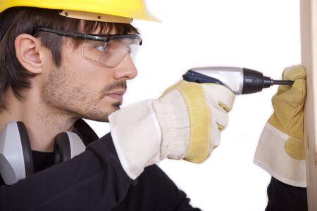 screwing: carpenter screwing a screw in woods Stock Photo