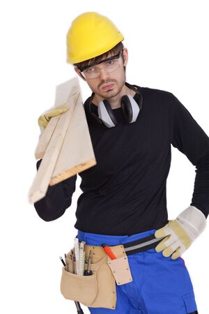 tired construction worker carrying wood photo