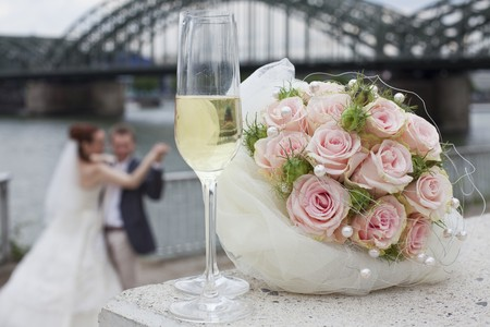dancing wedding couple - focus on glasses and bouquet in foreground photo