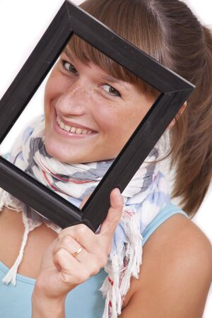 smiling woman looking through picture frame on white background photo