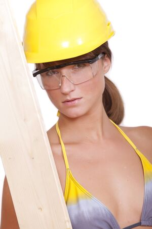 bikini construction: young woman worker in helmet holding wood on white background Stock Photo