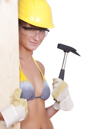 bikini construction: female worker in bikini with hammer on white background