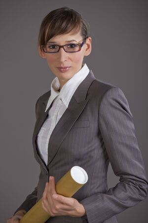 Portrait of business woman holding tube with blueprints over grey background photo