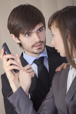 conflict situation in office - frustrated man talking to woman with phone photo