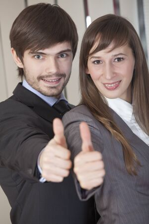 businesswoman and businessman holding their hands in sign - thumbs up photo