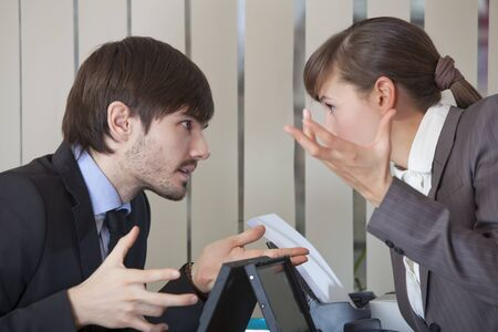 business disagreement: frustrated man and woman discussing by the work in office