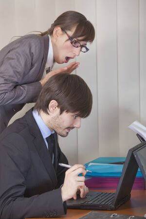 office scene - astounded woman looking over man shoulder at his computer photo