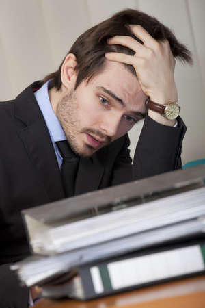 office scene - frustrated and overworked man with many folders photo