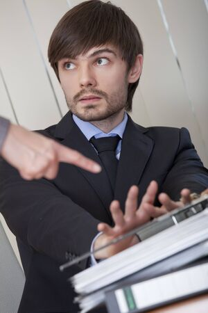 office scene - business man rejecting office work photo