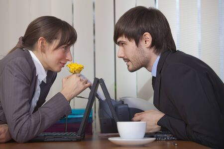 relationship by the work - happy man giving flower to woman