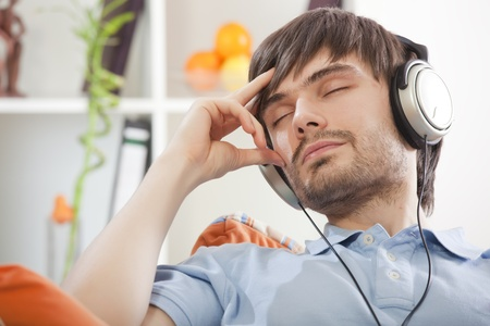 young man with closed eyes and earphones hearing music photo