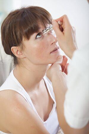 ocular: doctor shines a light into eye to check vision ocular health