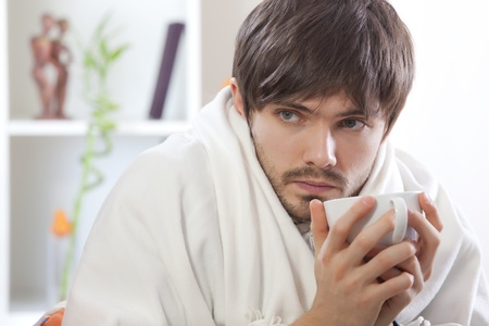 man with cup tea sitting on sofa with flu photo