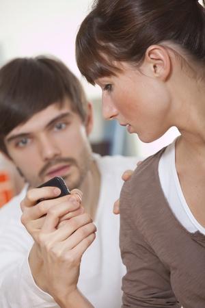 celos: hombre de celos, tratando de leer un mensaje en celular  Foto de archivo