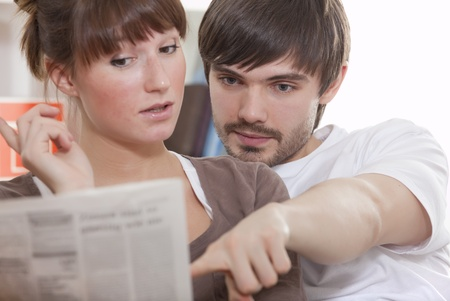 young couple at home reading newspaper together Stock Photo
