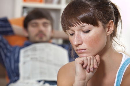 sad woman in front of sleeping man with newspaper photo