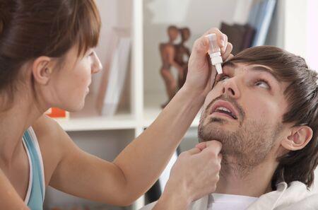 ocular: Woman dripping man eye with eyes drops