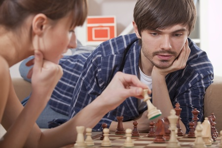 young couple playing chess game at home photo