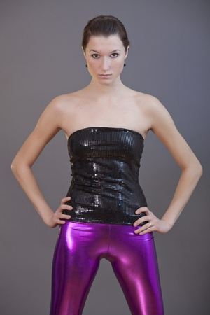 sexy party girl in shiny pants posing over grey background photo