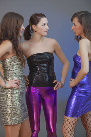 portrait of three party girls talking over grey background photo
