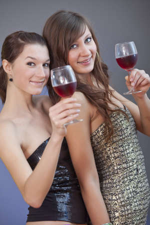 two party girls with alcohol drinks over grey background photo