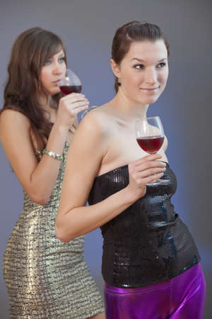 two party girls with drinks on disco - shot over grey background photo