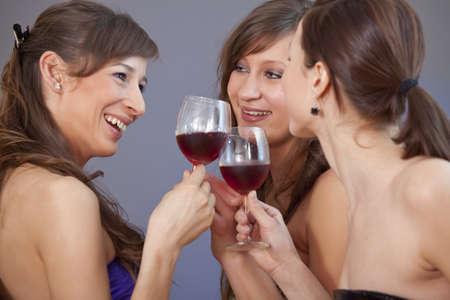 three party girls celebrating over grey background photo