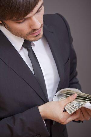 contando dinero: da�ado el hombre de negocios contando dinero sobre fondo gris Foto de archivo