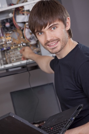 male computer technician with laptop in his hand repairing computer Stock Photo - 8572579