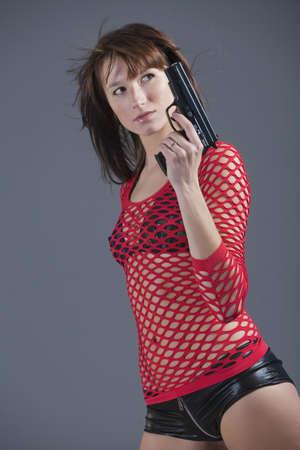mujer joven en ropa sexy posando con pistola sobre fondo gris
