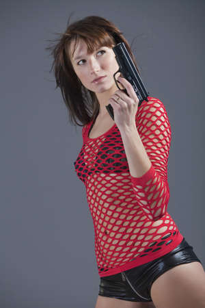 young woman in sexy clothes posing with gun over grey background photo