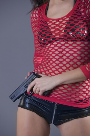 young woman in sexy clothes holding gun over grey background photo