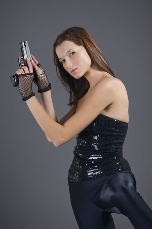 portrait of young woman in black leggings posing with gun photo