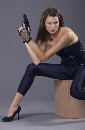 young woman in black leggings and high heels posing with gun photo