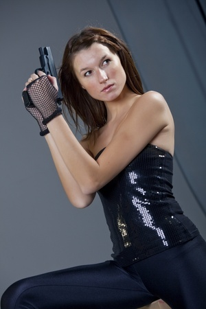 young woman in black leggigns with gun Stock Photo - 8572590