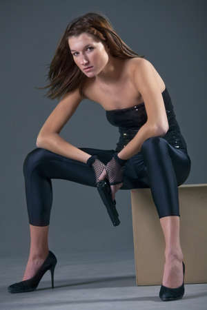 sexy woman in black leggigns with gun over grey background photo