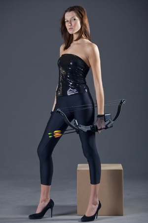 archery - young woman in black leggigns and high heels posing with bow and arrow photo