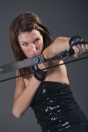 sexy female archer aiming over grey background Stock Photo - 8568397