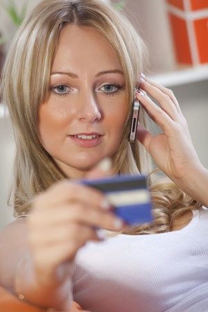 blond woman holding credit card and making purchase on cell phone photo