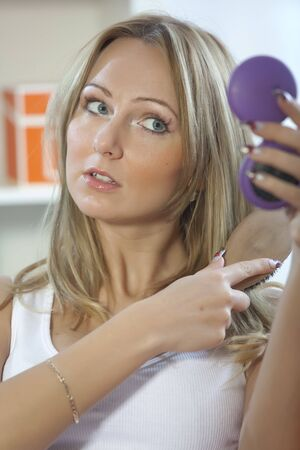 blond woman combing her hair with hairbrush on sofa photo
