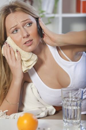woman with toothache talking with medical doctor on mobile phone photo