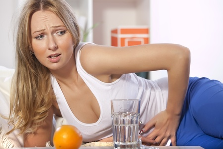 stomach flu: blond woman holding her stomach in pain on the sofa Stock Photo