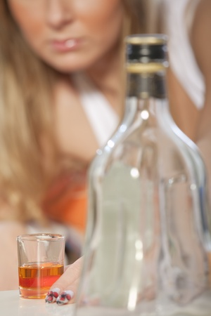 Young woman addicted to alcohol - focus on glass photo